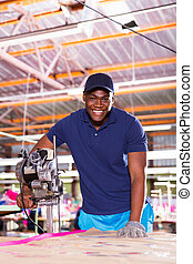 african american textile factory worker using fabric cutter