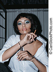 portrait of african american woman in cuffs with cigarette in hand