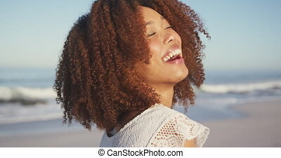 Front view of an African American woman enjoying time in the sun on a tropical beach, looking to camera and smiling, in slow motion