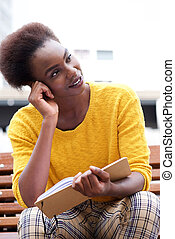 african american woman sitting outside with books and thinking