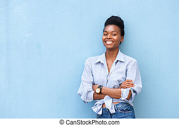 african american woman smiling with arms crossed on blue background