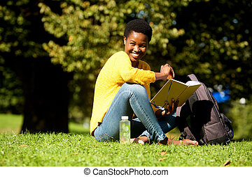 african american woman smiling with book in park