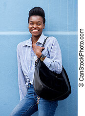 african american woman smiling with handbag against blue wall