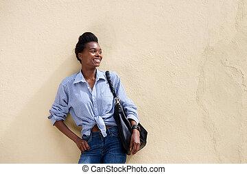 african american woman smiling with handbag