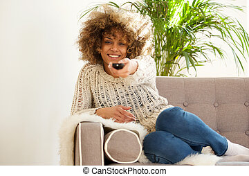 african american woman smiling with tv remote control
