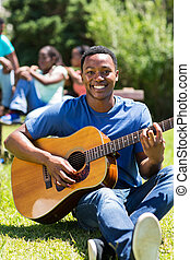 african college student playing guitar
