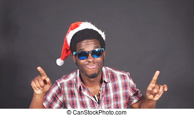 Portrait of African man having fun dancing in hat of Santa claus, slow motion.