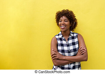 african woman smiling against yellow background