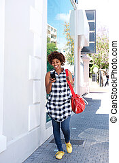 african woman walking with cellphone and bag in the city