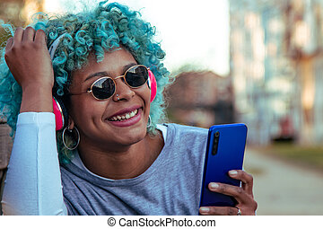 portrait of afro american girl on the street smiling with mobile phone and headphones