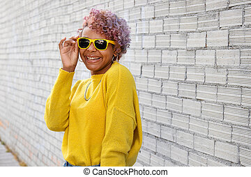 portrait of afro american girl smiling with sunglasses on the street