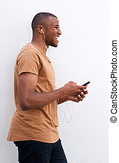 Portrait of afro american man listening music against white background