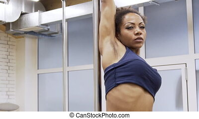 Portrait of afroamerican female dancer, who is turning around the pole in modern gym.
