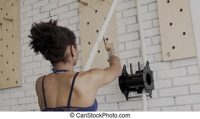 Portrait of afroamerican woman who is pulling the rope in luxury gym. Sportswoman in blue sport top is standing in front of the white brick wall with black equipment on it and training her musucular arms with silver armlets on.