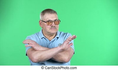 Portrait of aged man with mustache in glasses having gray hair in blue t-shirt strictly gesturing with hands crossed making X shape meaning denial saying NO, isolated over green background. Green screen