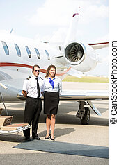 Portrait Of Airhostess And Pilot Standing Against Private Jet