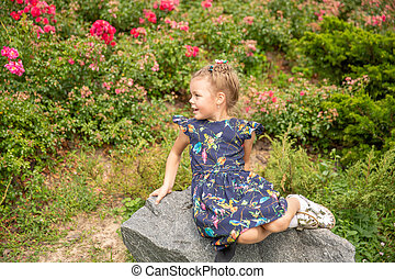 alone girl sitting on the stone in park