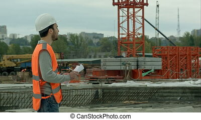Portrait of  amale site contractor engineer with helmet holding blueprint paper at construction site