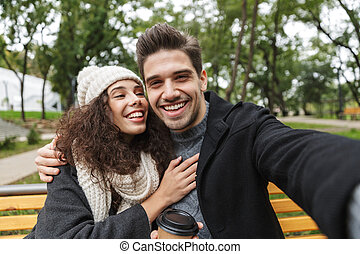 Portrait of amazing couple man and woman 20s taking selfie photo, while sitting on bench in green park