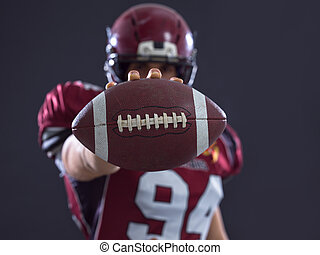 american football player showing football to camera