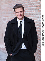 elegant young business man posing next to a brick wall with his hands in his pockets while looking amused into the camera, with a smile on his face