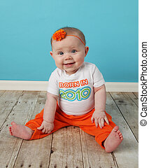 Born in 2010 - Portrait of an adorable baby girl sitting in...