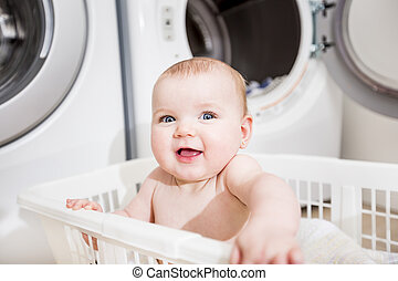 Portrait of an adorable baby sitting in a laundry basket