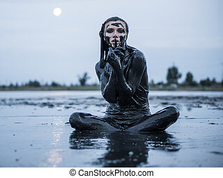 Portrait of an Adorable Caucasian Girl Sitting and posing Smeared with a Healthy Black Mud in old Firth