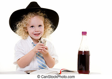 Portrait of an adorable curly haired blond little three year old boy wearing white shirt and tie and a black fedora practicing the Jewish Sabbath ritual
