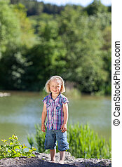 Portrait of an adorable little girl at the lake