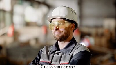 Portrait of an adult construction worker in a protective helmet, a person enjoys the process of building high-quality construction of his subordinates