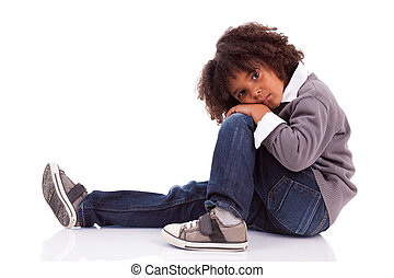 Portrait of an african american little boy sitting on the floor