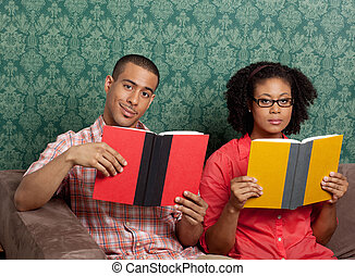 African American man and woman with books at home