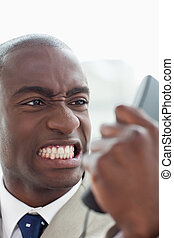 Portrait of an angry businessman looking at his phone...