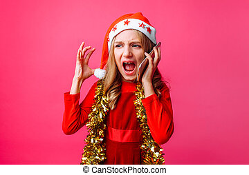 Portrait of an angry schoolgirl girl in Santa hat and tinsel on the neck, emotionally talking on the phone and screaming, isolated on red background