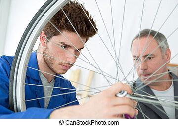 portrait of an apprentice fixing a wheel