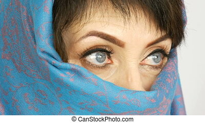 Portrait of an arabic middle aged adult woman with unusual beautiful big blue eyes with long eyelashes in traditional islamic cloth niqab or blue burqa. Close up of a beautiful muslim woman