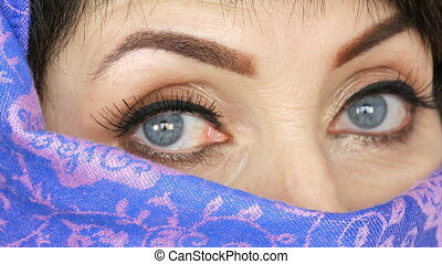 Portrait of an arabic middle aged adult woman with unusual beautiful big blue eyes with long eyelashes in traditional islamic cloth niqab or burqa. Close up of a beautiful muslim woman