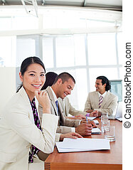 Portrait of an Asian businesswoman and her team during a presentation in a company