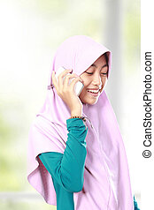 Portrait of an asian muslim kid talking on the cell phone
