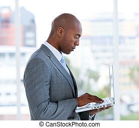Portrait of an assertive businessman working at a laptop