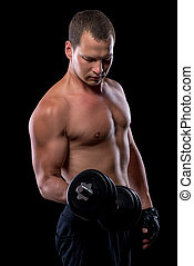 portrait of an athlete with dumbbells while training in a dark room