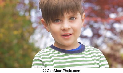 Portrait of an attractive adorable happy smiling little boy in slow motion