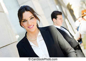 Portrait of an attractive businesswoman standing outside of company building. Couple working.