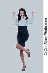 Portrait of an attractive businesswoman with her arms raised in celebration.