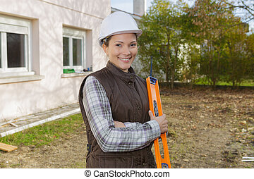 portrait of an attractive female construction worker with level