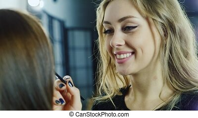 Portrait of an attractive female makeup artist at work