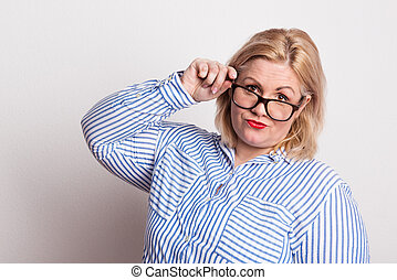 Portrait of an attractive overweight woman with glasses in studio.