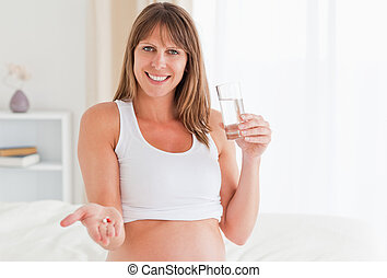 Portrait of an attractive pregnant female taking a pill while sitting on a bed in her apartment