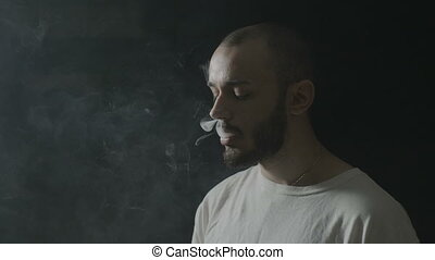 Portrait of an attractive teenager boy vaping and making...